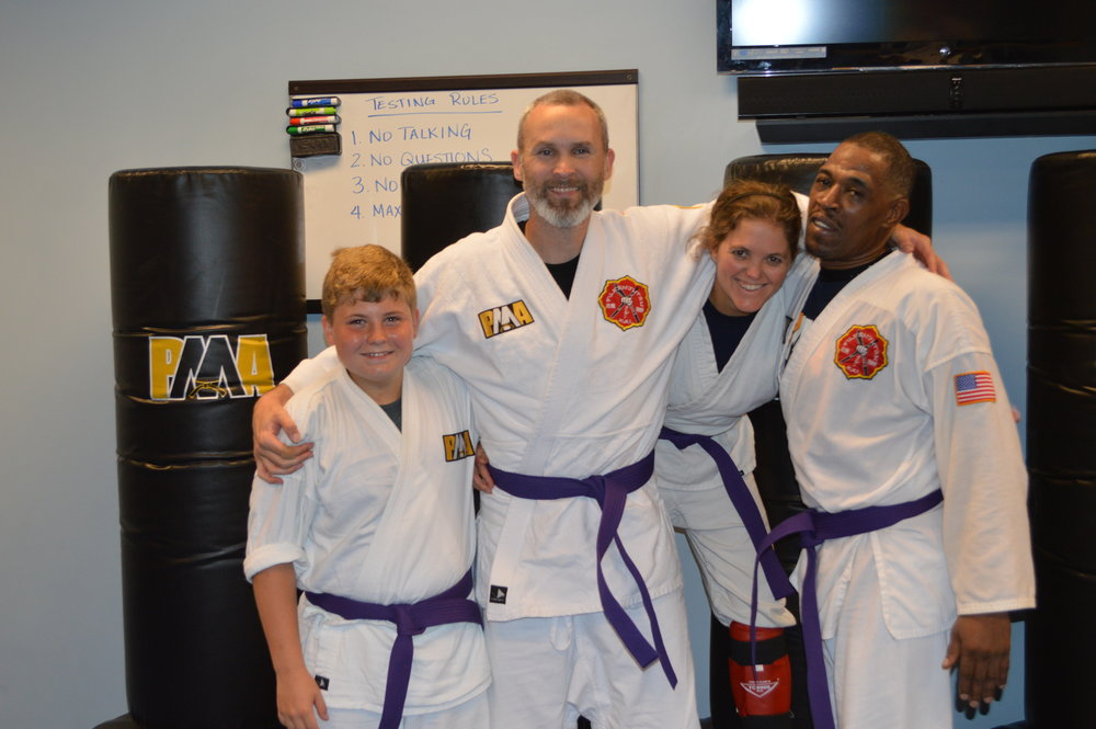 Kristie with some of her training partners after testing for Purple Belt in Kenpo. Purple belt is a big step in a student's Kenpo journey as it is the first intermediate rank, and the student switches to a black uniform.