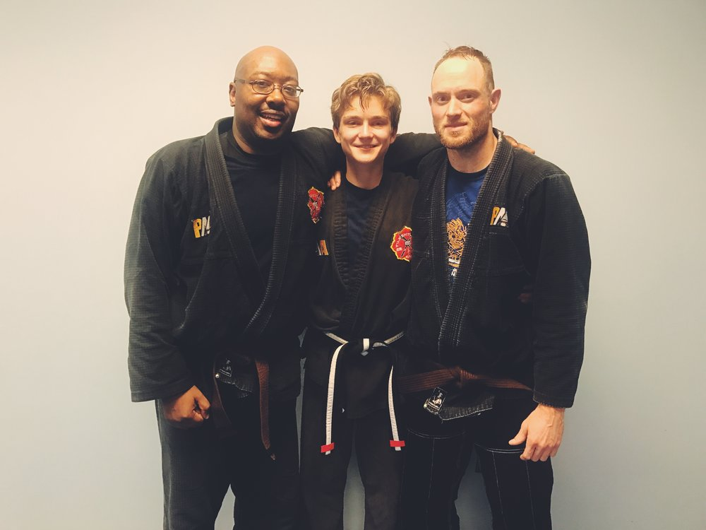 "December 2016 - Iain tested for his first degree on his Junior Black Belt, alongside Monty Blalock and Matt Thomas. At PMA, when a child reaches Brown Belt but is not old enough to take the Black Belt test yet, we test them for a ""Junior Black Belt,"" which is the belt you see in this photo with the white stripe. Then, they can earn degrees (the red stripes) on their Junior Black Belt, until they turn 18 and are selected to take the test for their full Black Belt."