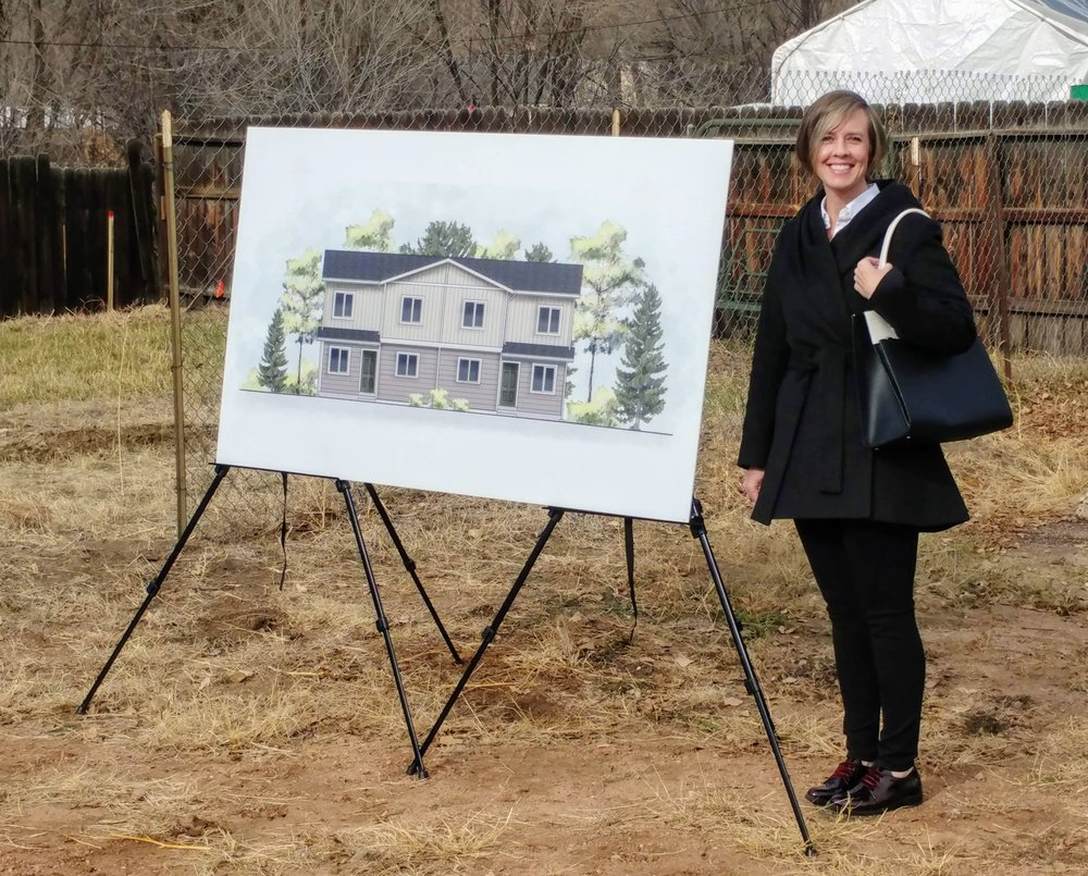 Shannon Baumgartner at the Habitat for Humanity Ground Blessing Ceremony next to the home elevation designed by LGA Studios