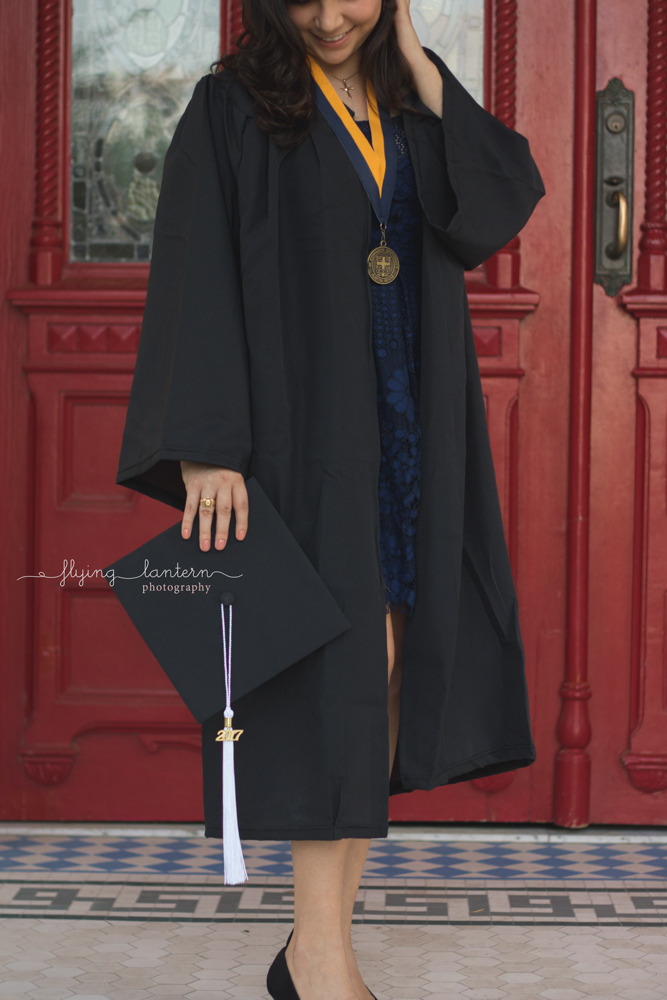 college graduate of St. Edward's University in front of red doors