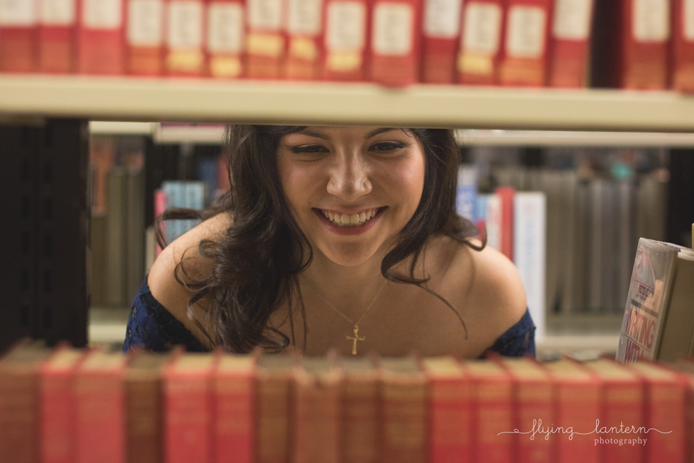 girl senior portraits in library looking through bookstacks