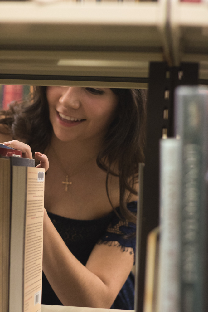 girl senior portraits in library looking through book shelves