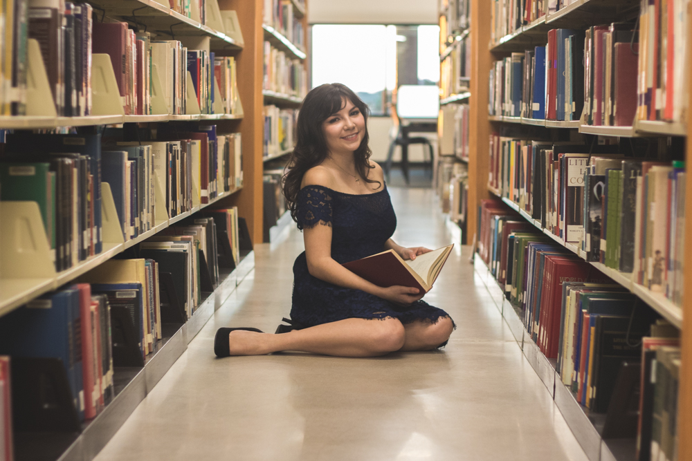 girl senior portraits in library reading a book