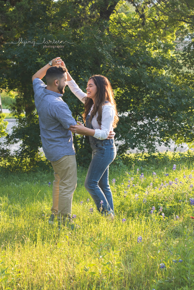 couple dancing in field of flowers during sunset