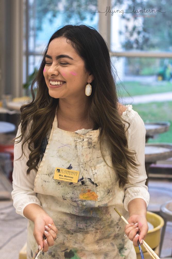 senior portrait of girl holding paintbrushes and laughing