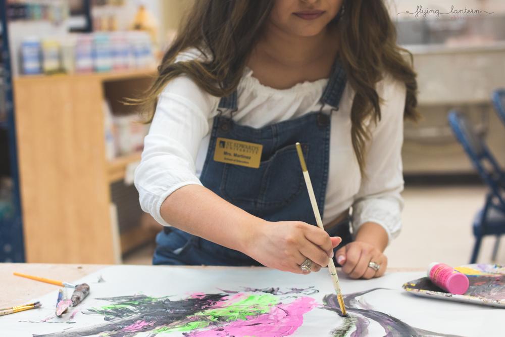 lifestyle of college senior painting in art studio