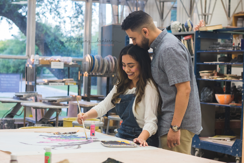 couple lifestyle of him standing next to her watching her while she paints