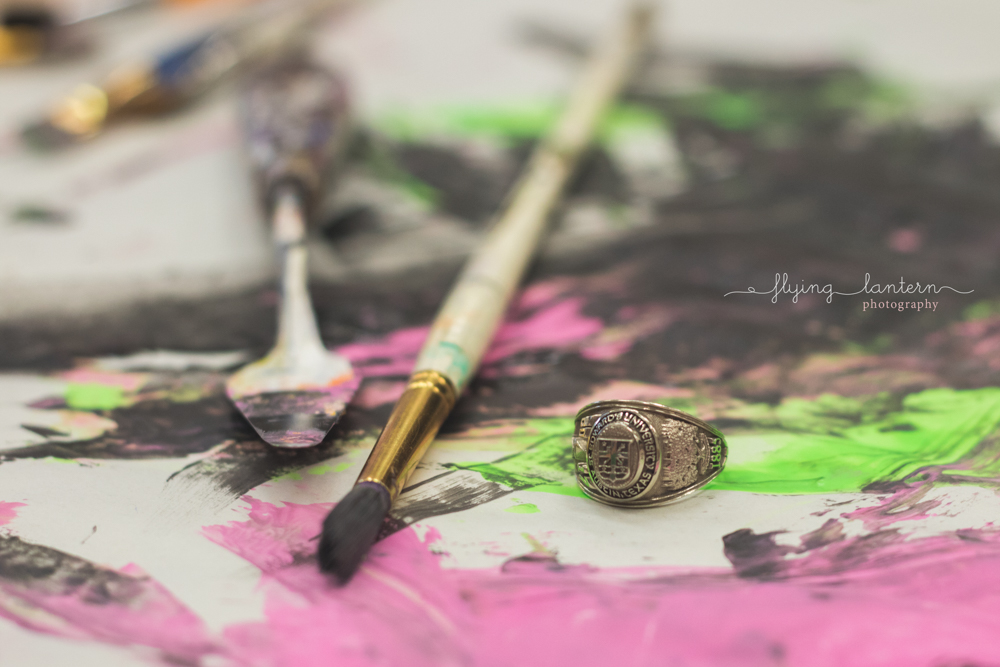 close up shot of St. Edward's university ring on painting paper with paintbrush