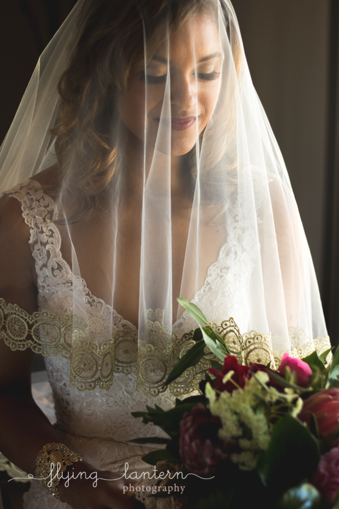 bride with veil over face and holding bouquet
