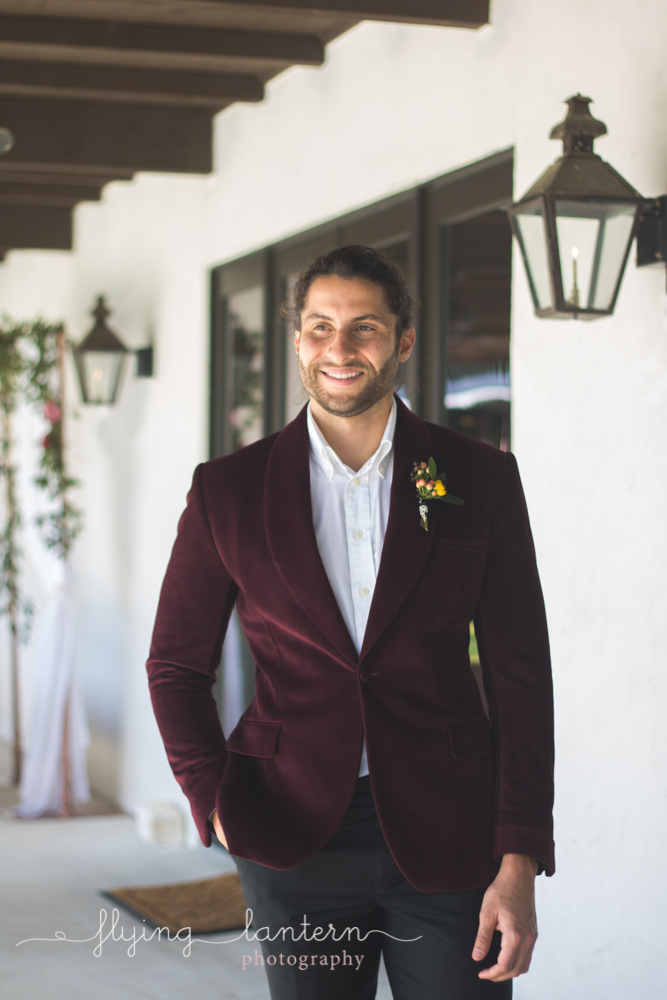 groom in burgundy suit looking to side