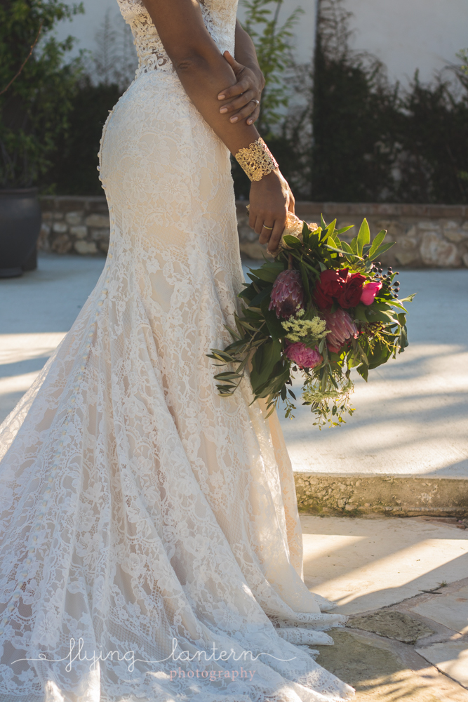 bride holding bouquet down lace dress