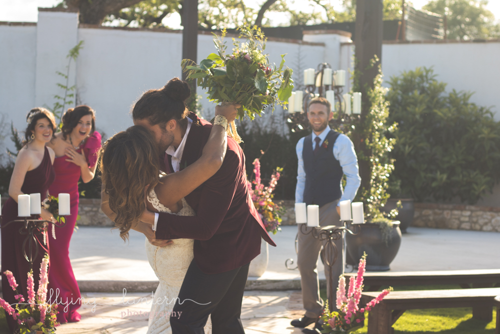 bride and groom kiss after walking down aisle and everyone cheers