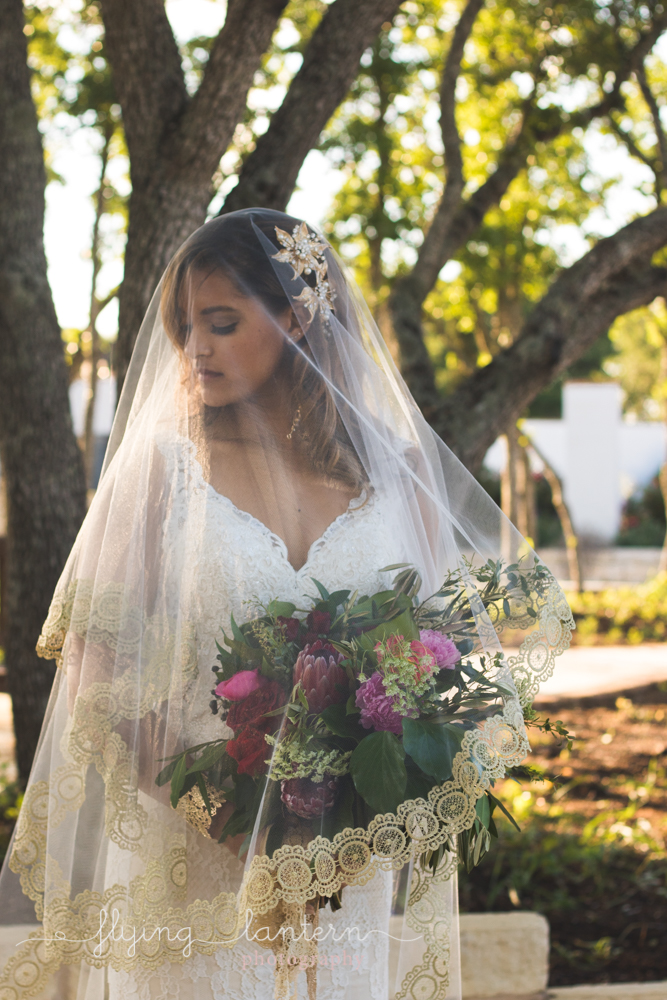 bride outside with veil over face looking to the left and down