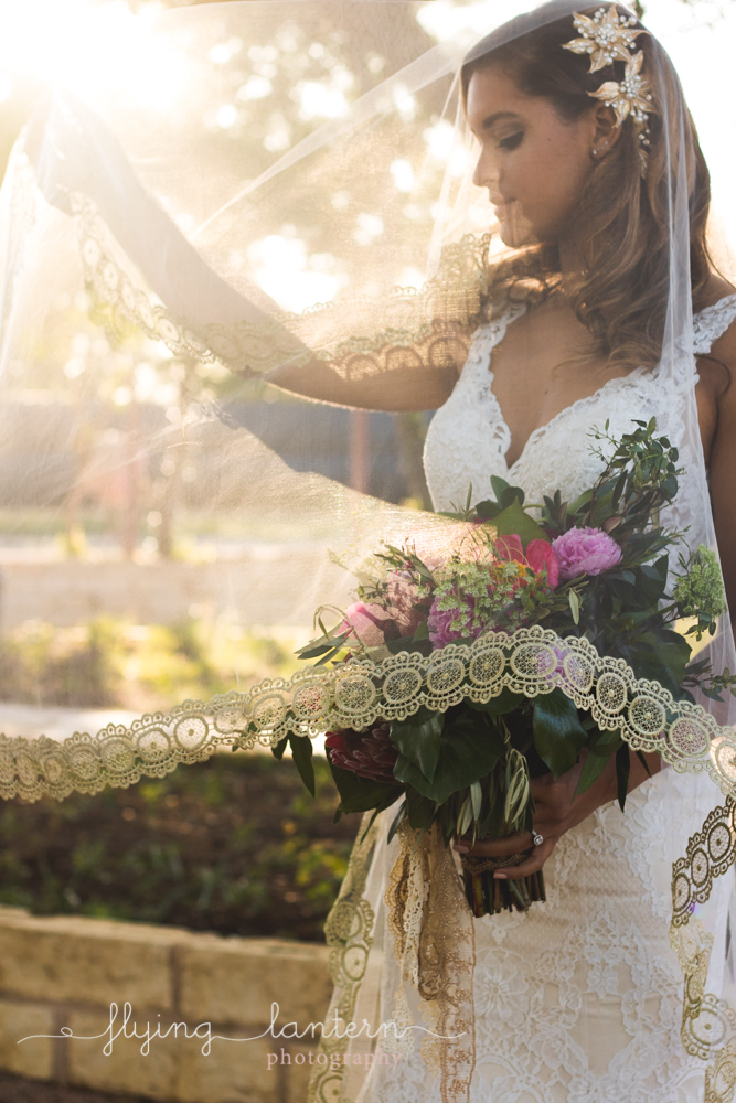 bride holding veil up to catch the sun