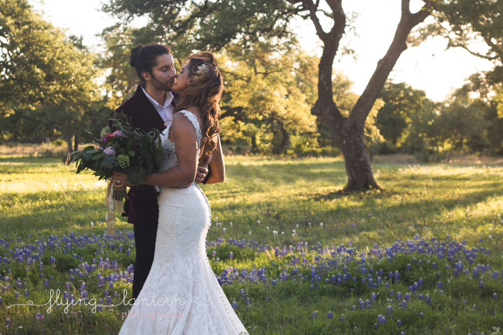 bride and groom standing in field of bluebonnets kissing