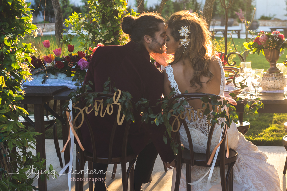 bride and groom sitting for reception kissing