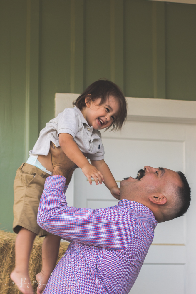dad lifting son into air smiling