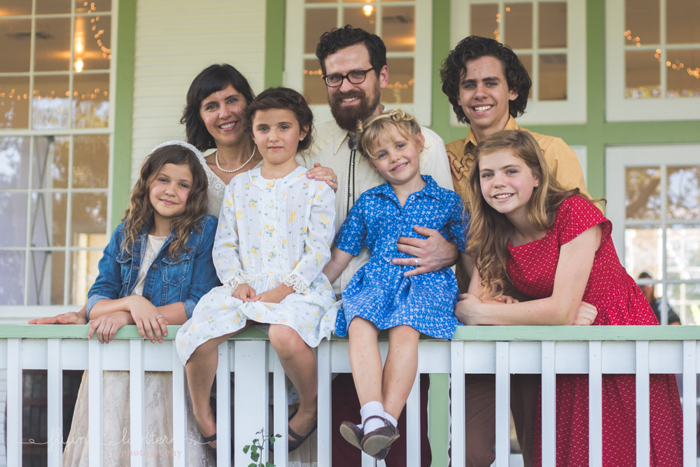 family of seven standing on porch looking at camera