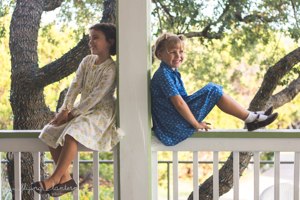 little girls sitting on deck bannister