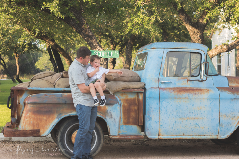 dad holding son and standing in front of truck