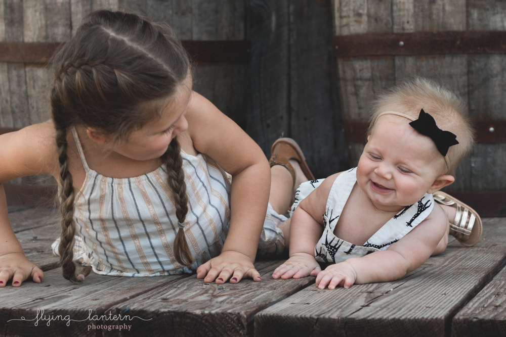 older sister and baby sister looking at each other and giggling