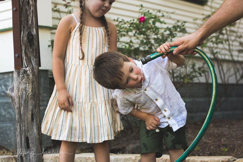 little boy drinking water from hose and sister watching