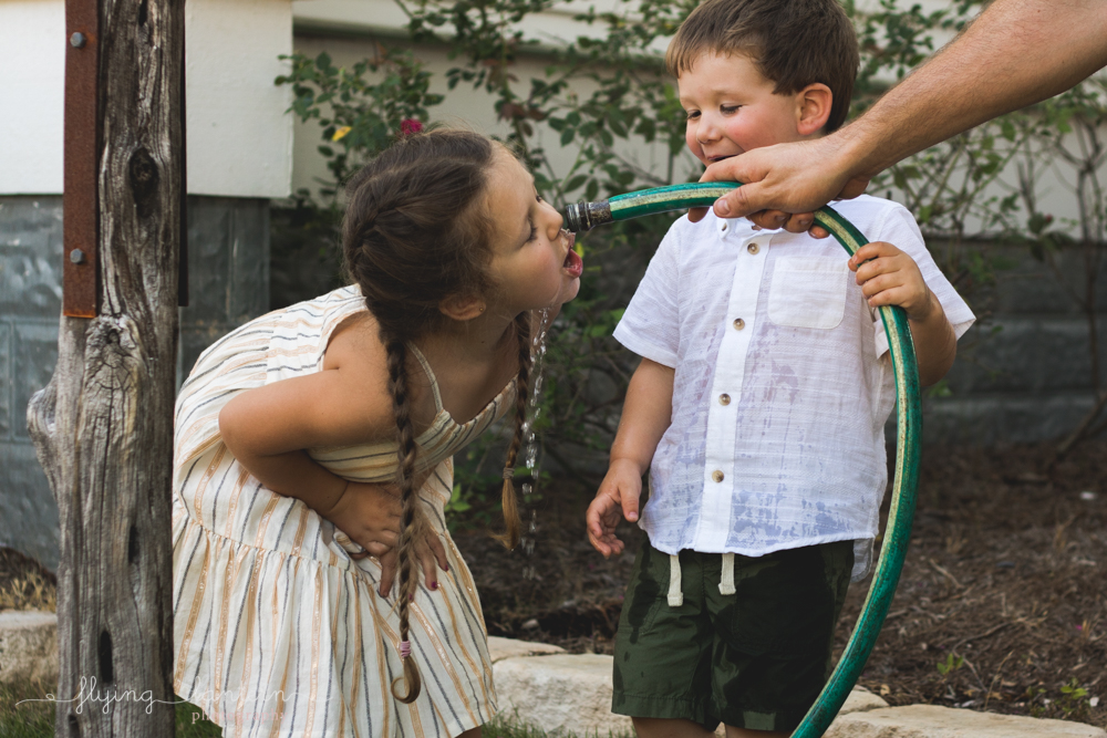 father gives water to daughter through hose
