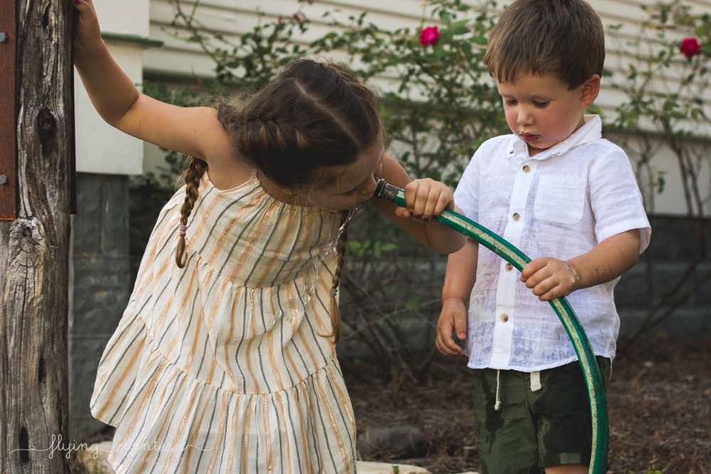 little girl drinks water out of hose and brother holds it