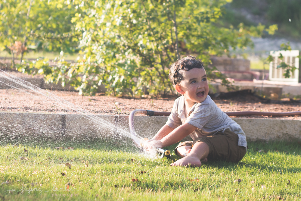 two year old boy playing in sprinkler and looking away