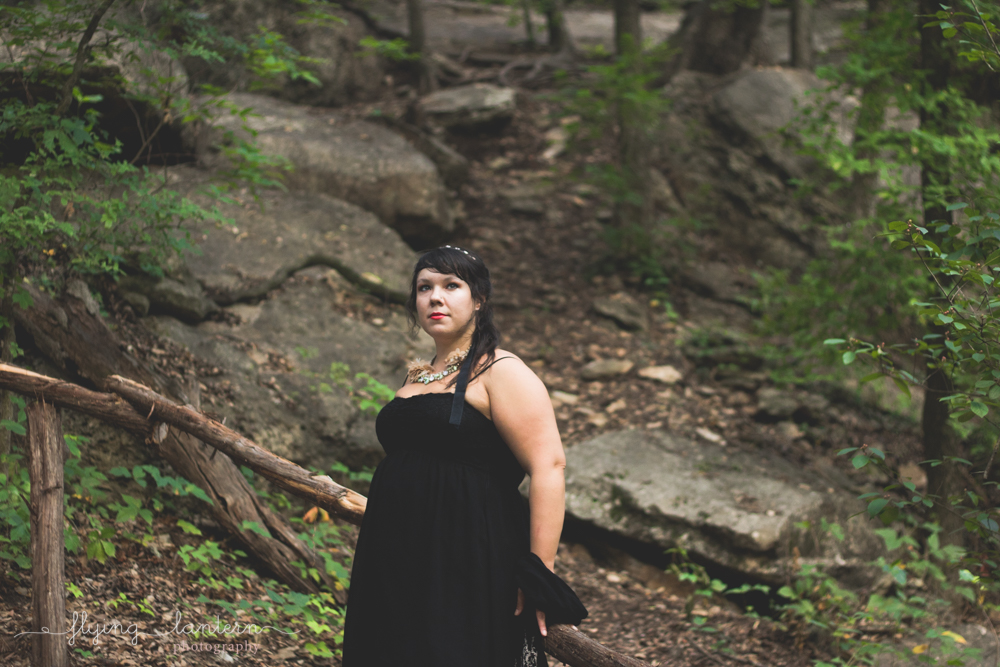 girl standing in forest wearing black dress