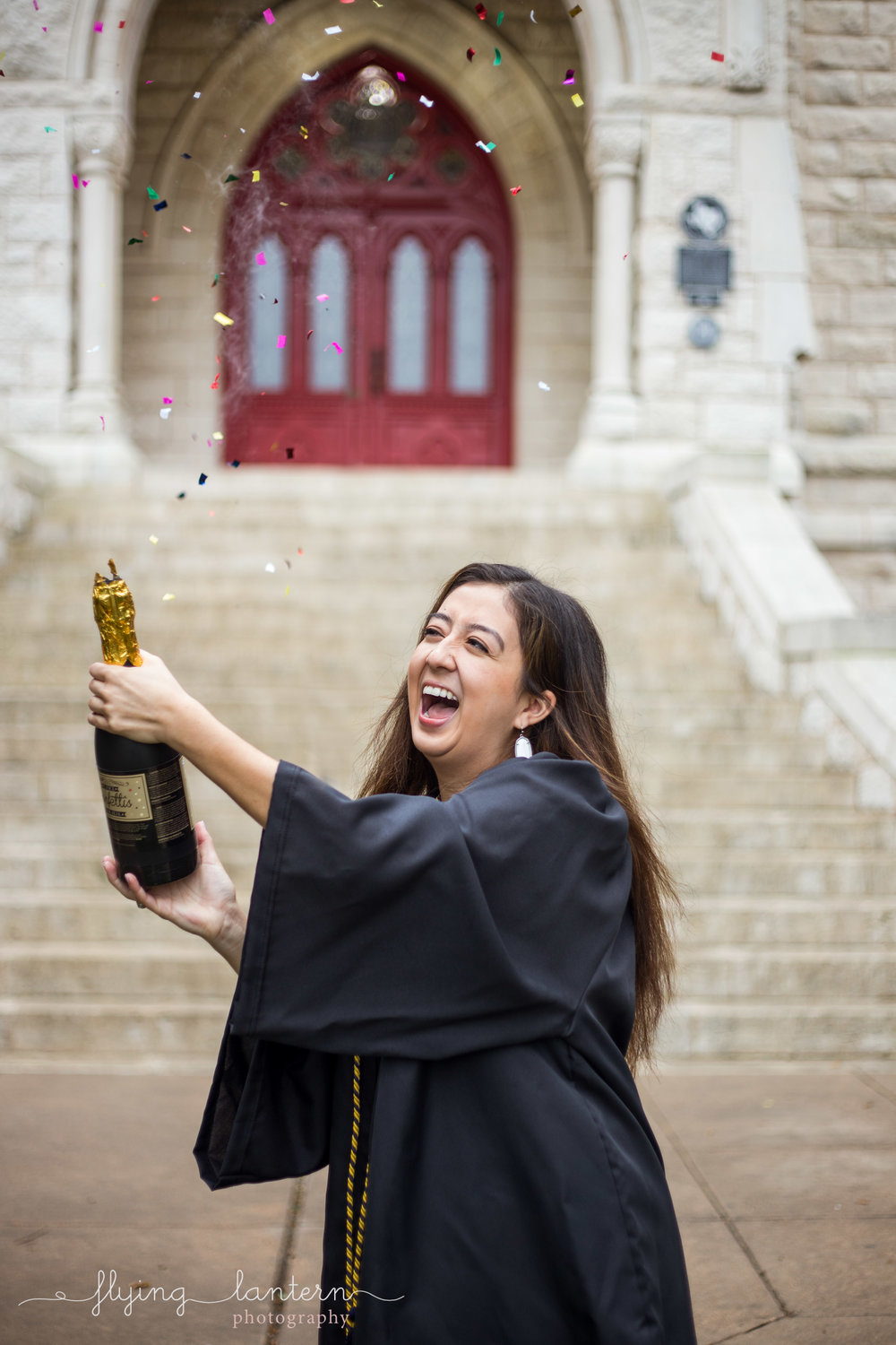 Girl senior portrait at st. edward's university in front of main building popping champagne confetti by Erin Reas of flying lantern photography