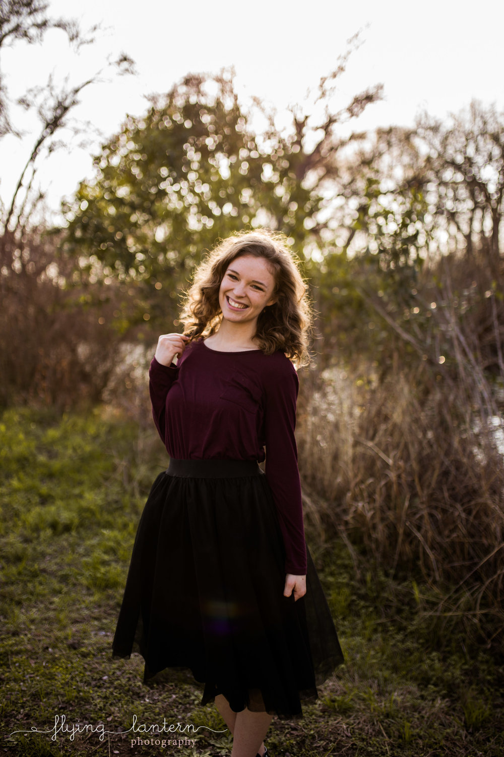 Girl senior portrait at mckinney falls state park wearing black tulle skirt and maroon top by Erin Reas of flying lantern photography