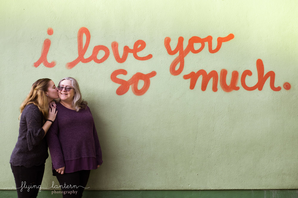family lifestyle session mom and daughter on south congress in front of i love you so much sign in austin, texas by erin reas of flying lantern photography