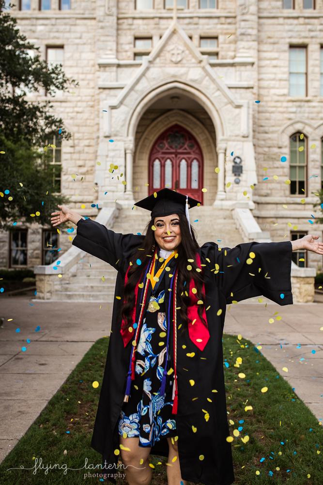 Senior Portrait in front of St. Edward's University main building throwing confetti photo by Erin Reas of Flying Lantern Photography