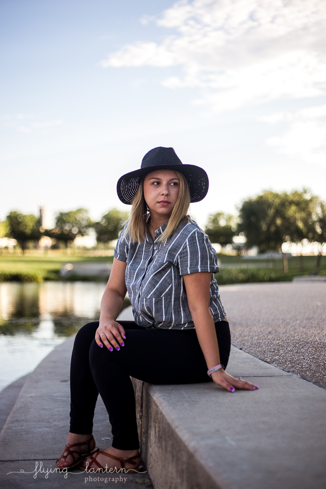 Austin food blogger lifestyle portrait session at Mueller Lake Park. Full body shot. Woman wearing striped grey top and black hat and black jeans. Photo by Erin Reas of Flying Lantern Photography