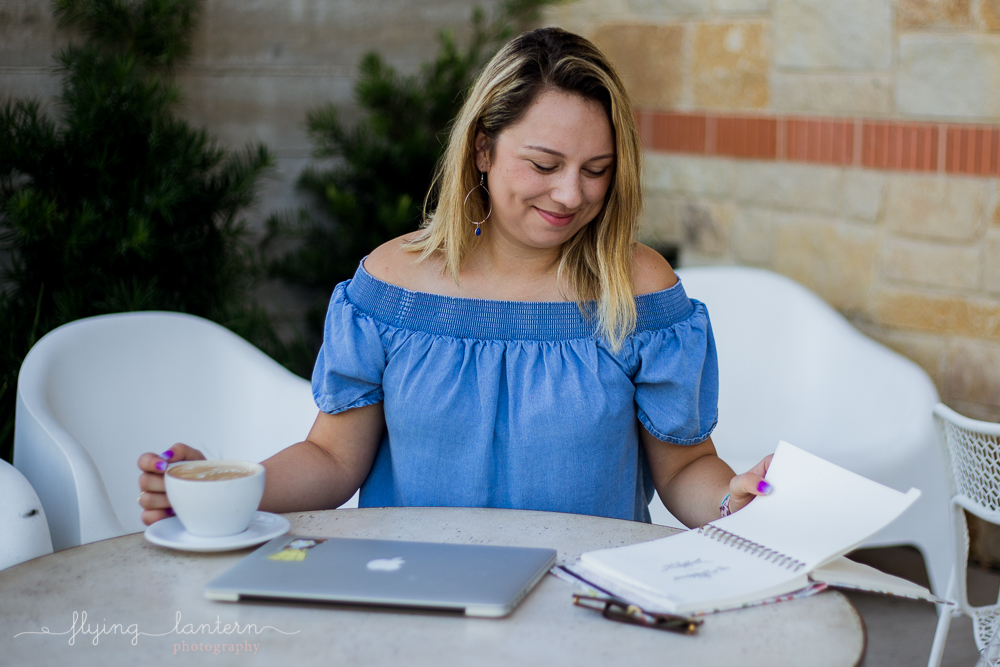 Austin food blogger lifestyle portrait session at Halcyon Mueller. Holding coffee and Rifle Paper planner. Woman wearing chambray off the shoulder blouse and black jeans. Photo by Erin Reas of Flying Lantern Photography
