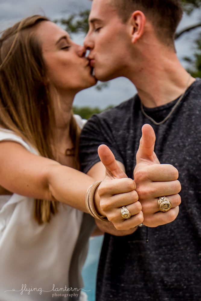 Texas A&M Married couple during extended family portrait session while together for family reunion weekend in Kingsland, TX. Making gig'em symbol with aggie rings. Photo by Erin Reas of Flying Lantern Photography