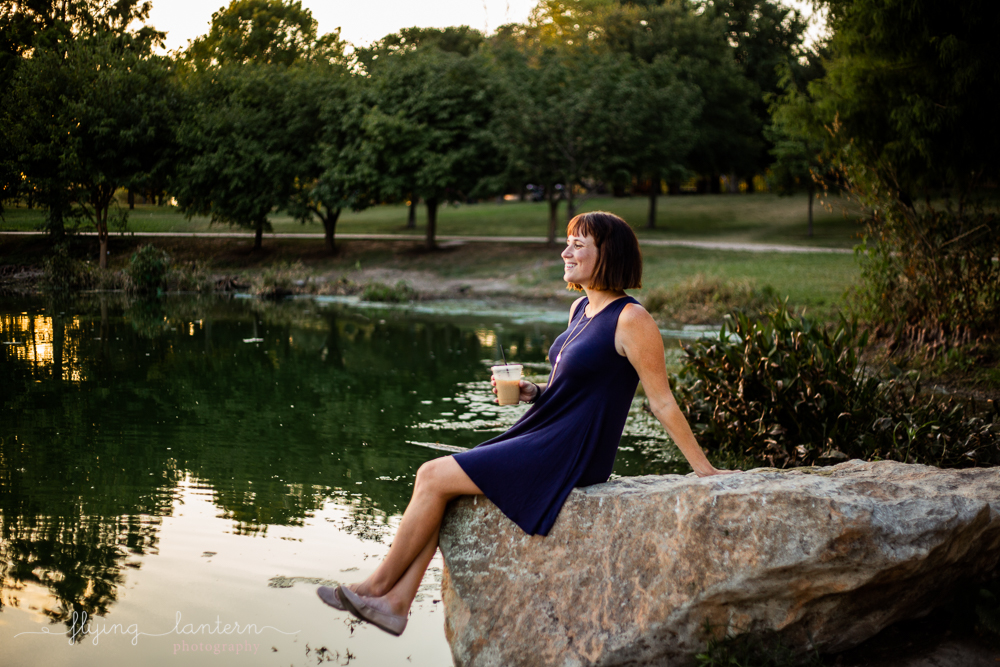 Austin blogger at mueller lake park lifestyle portrait sitting on rock looking out to lake photography by Erin Reas of Flying Lantern Photography