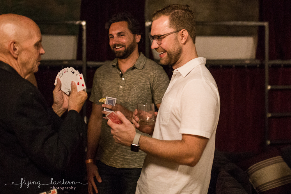 Magician playing card trick with two guys