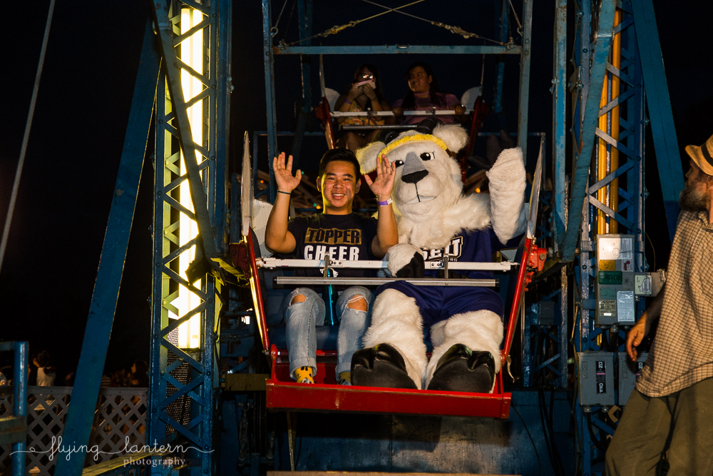 Topper and cheerleader waving on Ferris Wheel at Hillfest 2018 on St. Edward's University campus. Event photography by Erin Reas of Flying Lantern Photography