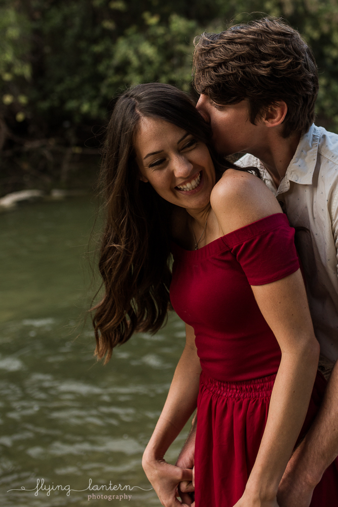 Couples portrait at Walnut Creek Park in Austin, TX. Couple close and almost kissing and laughing. Girl back to boy. Photo by Erin Reas of Flying Lantern Photography