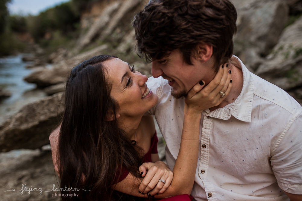 Couples lifestyle session at Walnut Creek Park in Austin, TX. Couple sitting and holding each other and laughing Photo by Erin Reas of Flying Lantern Photography