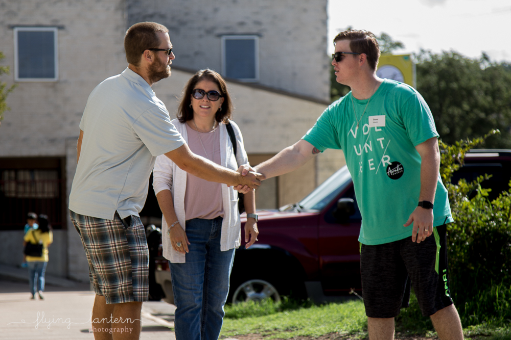 awaken church launch guests shaking volunteer's hand. event photography by erin reas of flying lantern photography