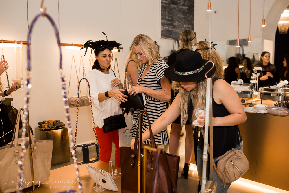 kelly wynne release women looking at hand purses. event photo by erin reas of flying lantern photography