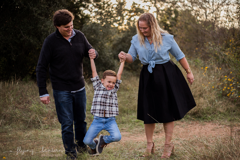 fun family portrait session where parents are swinging kid. photo by erin reas of flying lantern photography based in austin, tx