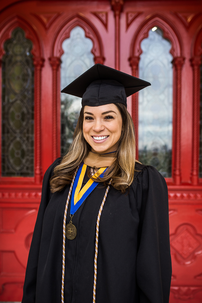 Graduate student at St. Edward's University in Austin, TX posing in front of red doors. Senior portrait by Erin Reas of Flying Lantern Photography.