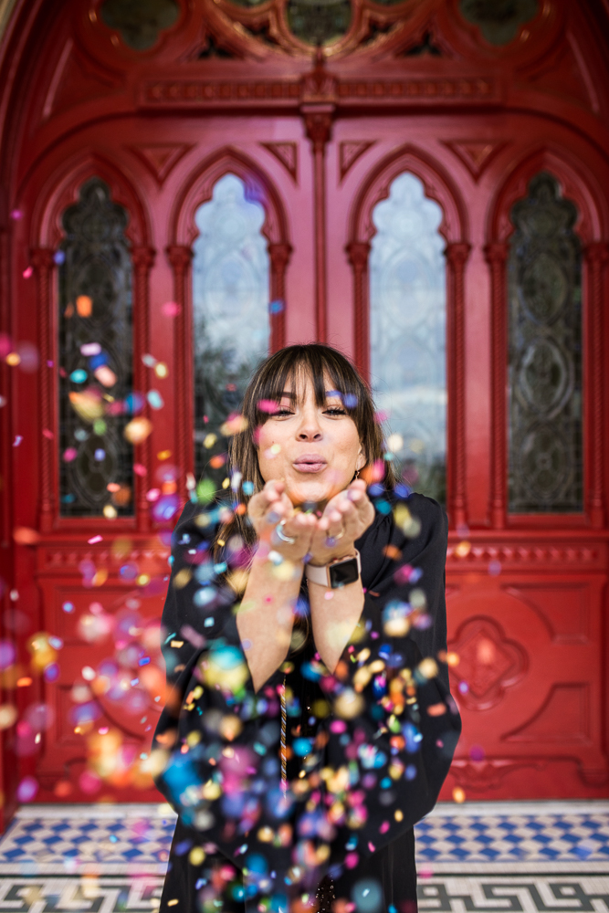 Graduate student at St. Edward's University in Austin, TX posing at main building in front of red doors blowing confetti. Senior portrait by Erin Reas of Flying Lantern Photography.