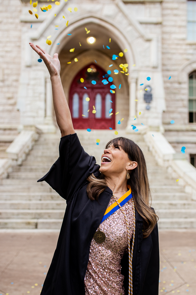 Graduate at St. Edward's University standing in front of Main Building throwing yellow and blue confetti. Senior portraits by Erin Reas of Flying Lantern Photography.