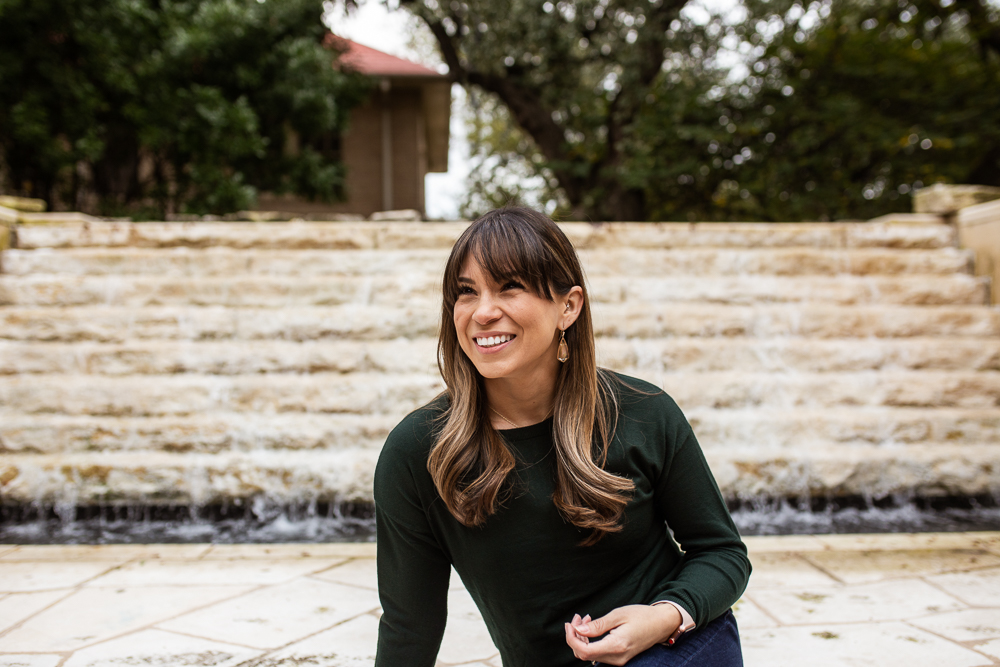 Graduation portraits at St. Edward's University in front of fountain. Senior portraits by Erin Reas of Flying Lantern Photography.