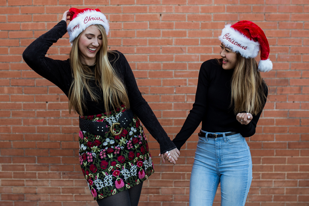 Friends photoshoot wearing Christmas Santa hats standing in front of brick wall in Downtown Buda. Photo by Erin Reas of Flying Lantern Photography.
